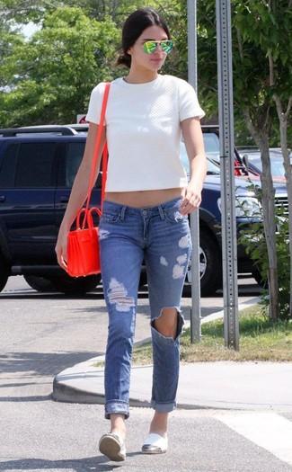 Как и с чем носить: белый стеганый укороченный топ, синие рваные джинсы скинни, белые эспадрильи из плотной ткани, красная кожаная сумка через плечо
