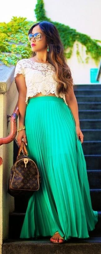 Как и с чем носить: бежевый укороченный топ крючком, зеленая длинная юбка со складками, светло-коричневые кожаные вьетнамки, темно-коричневая кожаная спортивная сумка с принтом