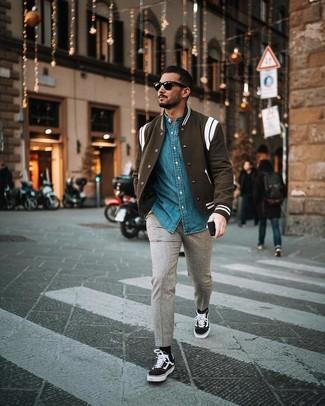 Как и с чем носить: черно-белая университетская куртка, синяя джинсовая рубашка, серые шерстяные брюки чинос, черно-белые низкие кеды из плотной ткани