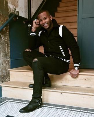 С чем носить черные рваные зауженные джинсы мужчине: Сочетание черно-белой университетской куртки и черных рваных зауженных джинсов - очень практично, и поэтому идеально для создания беззаботного повседневного  образа. Хочешь добавить в этот лук нотку классики? Тогда в качестве обуви к этому луку, выбирай черные замшевые ботинки челси.