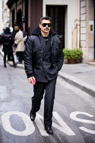 Как одеваться мужчине за 40: Черная университетская куртка в сочетании с темно-синим костюмом в вертикальную полоску без сомнений будет обращать на себя внимание прекрасных барышень. Преобразить ансамбль и добавить в него чуточку классики позволят черные кожаные ботинки челси.