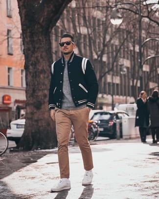 Как и с чем носить: черно-белая университетская куртка, серый свитер с круглым вырезом, светло-коричневые брюки чинос, белые низкие кеды