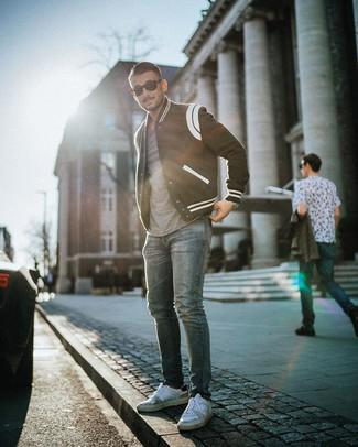 Как и с чем носить: черно-белая университетская куртка, серая футболка с круглым вырезом, синие джинсы, белые кожаные низкие кеды