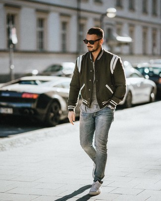 Как и с чем носить: черно-белая университетская куртка, серая футболка с круглым вырезом, голубые джинсы, белые низкие кеды
