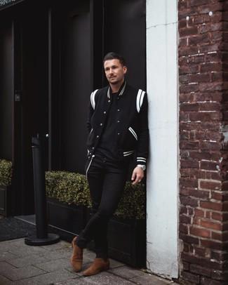 Как и с чем носить: черно-белая университетская куртка, черная футболка с круглым вырезом, черные зауженные джинсы, коричневые замшевые ботинки челси