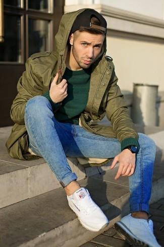 Как и с чем носить: оливковая фиштейл-парка, темно-зеленый свитер с круглым вырезом, синие зауженные джинсы, белые кроссовки