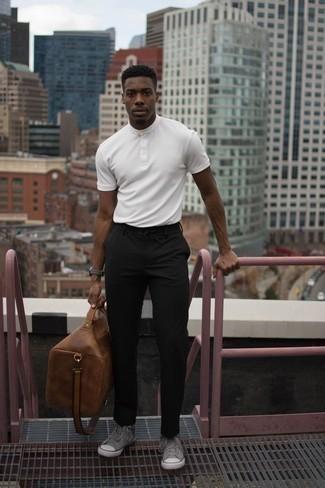 Коричневая кожаная дорожная сумка: с чем носить и как сочетать мужчине: Белая футболка на пуговицах и коричневая кожаная дорожная сумка помогут создать простой и комфортный образ для выходного дня в парке или вечера в баре с друзьями. Дополнив лук серыми высокими кедами из плотной ткани, получим поразительный результат.