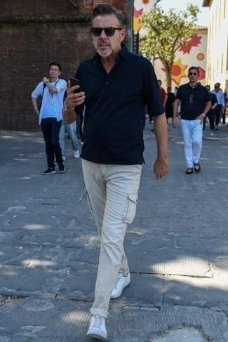 Как одеваться мужчине за 40: Темно-синяя футболка-поло и бежевые брюки карго позволят создать нескучный и модный образ. В тандеме с этим ансамблем наиболее удачно смотрятся белые низкие кеды из плотной ткани.