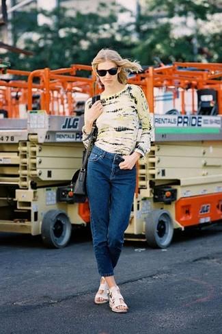 Модный лук: желтая футболка с длинным рукавом c принтом тай-дай, темно-синие джинсы, белые кожаные сандалии на плоской подошве, черная кожаная сумка через плечо