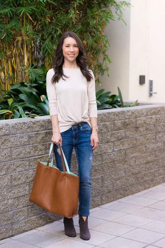 Как и с чем носить: бежевая футболка с длинным рукавом, синие рваные джинсы скинни, темно-серые замшевые ботильоны, табачная кожаная большая сумка