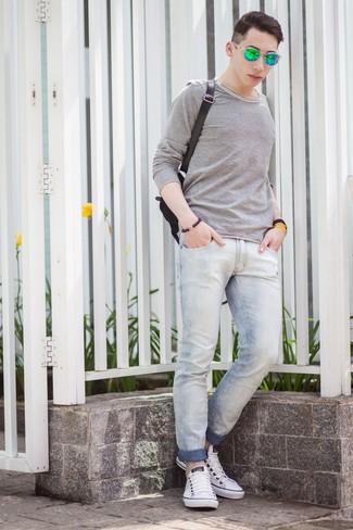 Как и с чем носить: серая футболка с длинным рукавом, голубые зауженные джинсы, белые низкие кеды, черный рюкзак из плотной ткани