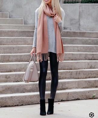 Как и с чем носить: серая футболка с длинным рукавом, черные кожаные леггинсы, черные замшевые ботильоны, розовая кожаная большая сумка