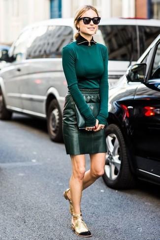 Модный лук: темно-бирюзовая футболка с длинным рукавом, темно-зеленая кожаная мини-юбка, золотые кожаные ботильоны на шнуровке с вырезом, темно-зеленый кожаный клатч