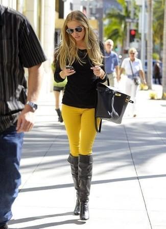 Модный лук: Черная футболка с длинным рукавом, Горчичные узкие брюки, Черные кожаные ботфорты, Черная кожаная сумка-мешок