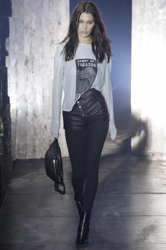 Как и с чем носить: бело-черная футболка с длинным рукавом с принтом, черные кожаные шорты, черные кожаные ботильоны, черная кожаная поясная сумка
