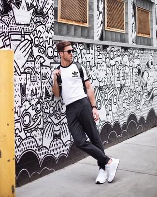 Модный лук: бело-черная футболка с круглым вырезом с принтом, темно-серые брюки чинос, белые кроссовки, черный кожаный рюкзак