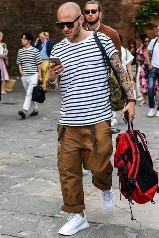 С чем носить коричневые брюки чинос: Бело-темно-синяя футболка с круглым вырезом в горизонтальную полоску в паре с коричневыми брюками чинос поможет подчеркнуть твой личный стиль и выигрышно выделиться из общей массы. Если сочетание несочетаемого импонирует тебе не меньше, чем проверенная классика, закончи этот образ белыми кроссовками.