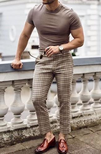 Бежевые брюки чинос в шотландскую клетку: с чем носить и как сочетать: Светло-коричневая футболка с круглым вырезом и бежевые брюки чинос в шотландскую клетку — необходимые вещи в арсенале мужчин с отличным чувством стиля. Уравновесить ансамбль и добавить в него чуточку классики помогут темно-красные кожаные лоферы с кисточками.