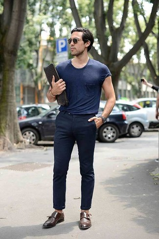 Как и с чем носить: темно-синяя футболка с круглым вырезом, темно-синие брюки чинос, коричневые кожаные монки с двумя ремешками, черный кожаный плетеный мужской клатч