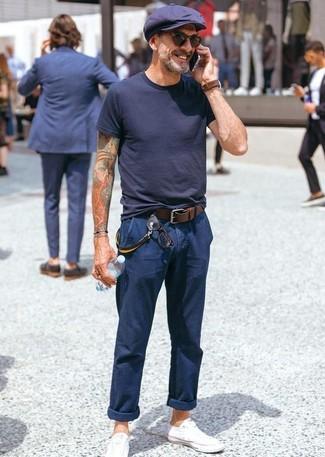 Как и с чем носить: черная футболка с круглым вырезом, темно-синие брюки чинос, белые низкие кеды из плотной ткани, темно-синяя кепка