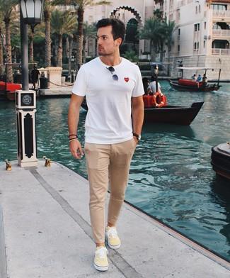 Как и с чем носить: белая футболка с круглым вырезом, светло-коричневые брюки чинос, желтые низкие кеды из плотной ткани, черные солнцезащитные очки
