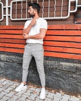 Мужские луки: Белая футболка с круглым вырезом в паре с серыми брюками чинос в шотландскую клетку однозначно будет привлекать внимание прекрасных женщин. Что же до обуви, бело-черные кожаные низкие кеды — самый достойный вариант.