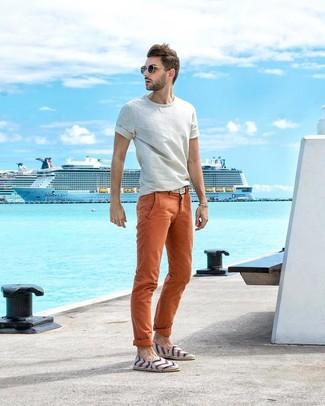 Как и с чем носить: белая футболка с круглым вырезом, оранжевые брюки чинос, белые эспадрильи из плотной ткани в горизонтальную полоску, белый плетеный ремень из плотной ткани