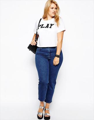 Как и с чем носить: бело-черная футболка с круглым вырезом с принтом, синие джинсы, серебряные кожаные массивные босоножки на каблуке, черная кожаная сумка через плечо