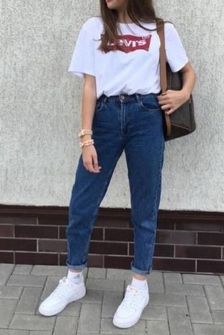Как и с чем носить: бело-красная футболка с круглым вырезом с принтом, синие джинсы, белые кожаные низкие кеды, темно-коричневый кожаный рюкзак