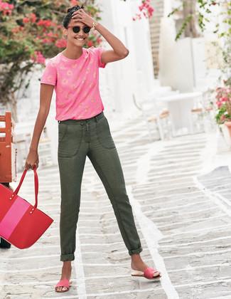 Как и с чем носить: ярко-розовая футболка с круглым вырезом с принтом, оливковые джинсы, ярко-розовые замшевые сандалии на плоской подошве, красная кожаная большая сумка