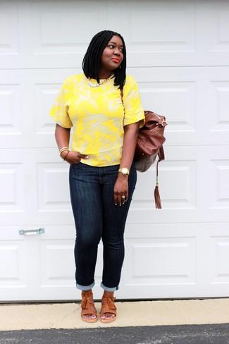 Как и с чем носить: желтая футболка с круглым вырезом с цветочным принтом, темно-синие джинсы скинни, оранжевые кожаные сандалии на плоской подошве, коричневый кожаный рюкзак
