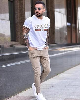 Как и с чем носить: белая футболка с круглым вырезом с принтом, бежевые зауженные джинсы, белые кожаные низкие кеды, серые солнцезащитные очки