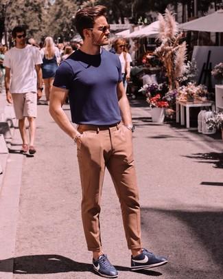 Как и с чем носить: темно-синяя футболка с круглым вырезом, светло-коричневые классические брюки, темно-синие кожаные низкие кеды, темно-коричневые солнцезащитные очки