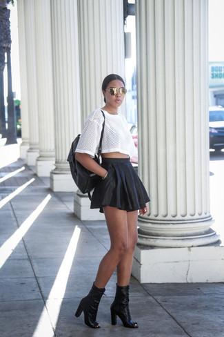 Как и с чем носить: белая футболка с круглым вырезом в сеточку, черная кожаная короткая юбка-солнце, черные кожаные ботильоны с вырезом, черный кожаный рюкзак