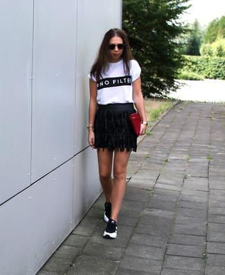 Как и с чем носить: бело-черная футболка с круглым вырезом с принтом, черная кожаная мини-юбка c бахромой, черно-белые кроссовки, темно-красный кожаный клатч