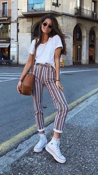Как и с чем носить: белая футболка с круглым вырезом, бело-красные узкие брюки в вертикальную полоску, белые высокие кеды из плотной ткани, коричневая кожаная сумка через плечо