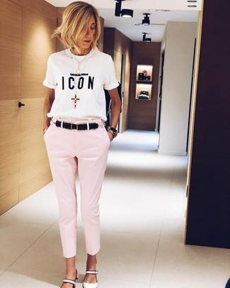 Как и с чем носить: бело-черная футболка с круглым вырезом с принтом, розовые узкие брюки, белые кожаные туфли, черный кожаный ремень