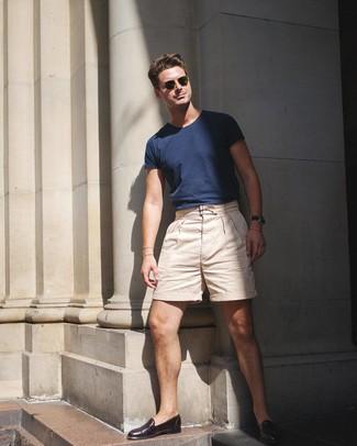 Как и с чем носить: темно-синяя футболка с круглым вырезом, бежевые шорты, темно-коричневые кожаные лоферы, оливковые солнцезащитные очки