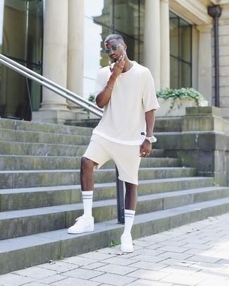 Как и с чем носить: бежевая футболка с круглым вырезом, бежевые шорты, белые низкие кеды, темно-синие солнцезащитные очки