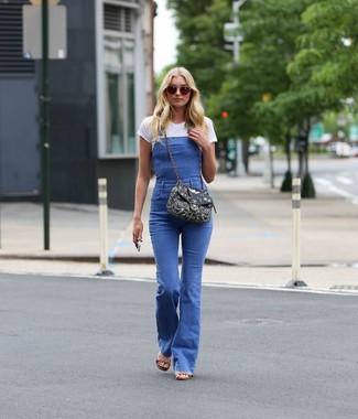 Как и с чем носить: белая футболка с круглым вырезом, синие джинсовые штаны-комбинезон, светло-коричневые кожаные босоножки на каблуке, черная сумка через плечо из плотной ткани с украшением