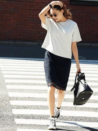 Как и с чем носить: серая футболка с круглым вырезом, черная кружевная юбка-карандаш, черно-белые высокие кеды из плотной ткани, черная кожаная большая сумка