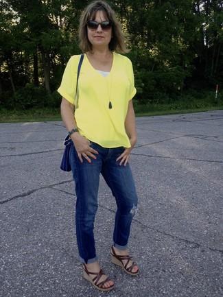 Как и с чем носить: желтая футболка с v-образным вырезом, синие рваные джинсы-бойфренды, коричневые кожаные босоножки на танкетке, синяя кожаная сумка через плечо