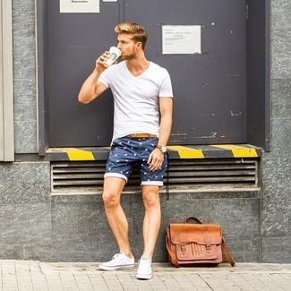 Как и с чем носить: белая футболка с v-образным вырезом, темно-синие шорты с принтом, белые низкие кеды из плотной ткани, светло-коричневая кожаная сумка почтальона