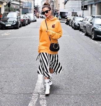 Как и с чем носить: оранжевый худи, бело-черное платье-миди в вертикальную полоску, белые кожаные ботильоны, черная кожаная сумка через плечо