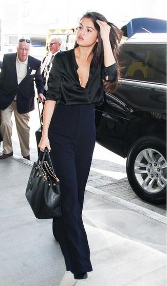 Как Selena Gomez носит Черная сатиновая блузка с длинным рукавом, Темно-синие широкие брюки, Черные кожаные туфли, Черная кожаная большая сумка
