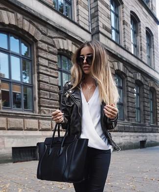 Как и с чем носить: черная кожаная косуха, белая шелковая блузка с длинным рукавом, черные джинсы скинни, черная кожаная большая сумка