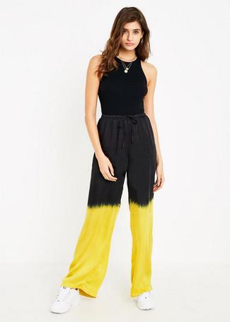 Как и с чем носить: черная майка, желтые широкие брюки c принтом тай-дай, белые кроссовки, золотая подвеска