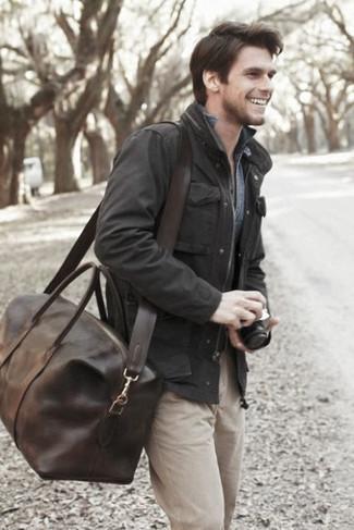 Как и с чем носить: черная полевая куртка, синяя джинсовая рубашка, бежевые брюки чинос, темно-коричневая кожаная дорожная сумка
