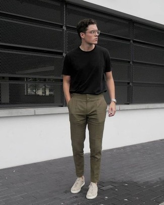 Модные мужские луки 2020 фото: Черная футболка с круглым вырезом в сочетании с оливковыми брюками чинос вне всякого сомнения будет обращать на себя внимание прекрасных девушек. В паре с этим ансамблем наиболее уместно будут смотреться бежевые низкие кеды.