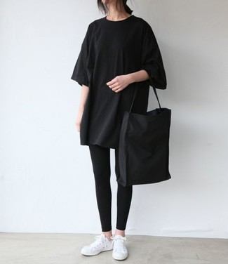 Как и с чем носить: черная футболка с круглым вырезом, черные леггинсы, белые низкие кеды, черная большая сумка из плотной ткани